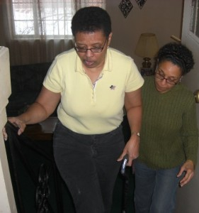 Caregiver Paulette helping her sister Maria up the stairs