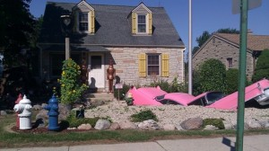 Pink car split in half and other assorted pieces form the landscape of a resident's front yard along South Lake Drive in Milwaukee.